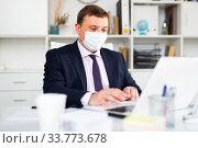 Купить «Man in protective face mask working at office», фото № 33773678, снято 6 июля 2020 г. (c) Яков Филимонов / Фотобанк Лори