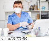 Купить «Man doctor in face mask working at laptop», фото № 33773690, снято 13 июля 2020 г. (c) Яков Филимонов / Фотобанк Лори