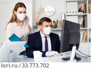 Manager in protective medical mask gives task to assistant. Стоковое фото, фотограф Яков Филимонов / Фотобанк Лори