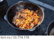 Купить «Pieces of meat cooking in a large cauldron with carrot», фото № 33774178, снято 5 октября 2019 г. (c) FotograFF / Фотобанк Лори