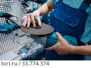 Male worker choosing edged disc in tool store. Стоковое фото, фотограф Tryapitsyn Sergiy / Фотобанк Лори