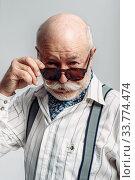 Купить «Elderly man with mustache poses in sunglasses», фото № 33774474, снято 7 февраля 2020 г. (c) Tryapitsyn Sergiy / Фотобанк Лори