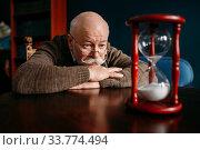 Elderly man looking on sandglass in home office. Стоковое фото, фотограф Tryapitsyn Sergiy / Фотобанк Лори