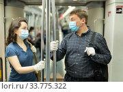 Купить «Man and woman in medical masks chatting in subway car», фото № 33775322, снято 4 июля 2020 г. (c) Яков Филимонов / Фотобанк Лори