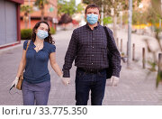 Couple in protective medical masks against coronavirus communicate on street. Стоковое фото, фотограф Яков Филимонов / Фотобанк Лори