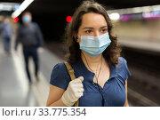 Купить «Woman in mask with earphones on subway station», фото № 33775354, снято 24 мая 2020 г. (c) Яков Филимонов / Фотобанк Лори