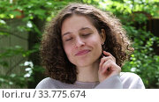 Portrait of a beautiful young brunette girl with curly hair on a green background in a park on a sunny summer day. Стоковое видео, видеограф Алексей Кузнецов / Фотобанк Лори