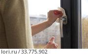 Купить «woman cleaning window handle with sanitizer tissue», видеоролик № 33775902, снято 10 мая 2020 г. (c) Syda Productions / Фотобанк Лори
