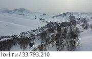 Купить «Aerial video of winter road and trees under snow in Altai. Siberia, Russia», видеоролик № 33793210, снято 30 апреля 2020 г. (c) Serg Zastavkin / Фотобанк Лори