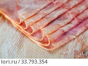 Купить «Sliced appetizing ham closeup wooden board», фото № 33793354, снято 31 мая 2020 г. (c) Яков Филимонов / Фотобанк Лори