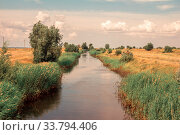 Купить «A large artificial canal filled with water for irrigation of fertile land.», фото № 33794406, снято 9 июля 2013 г. (c) Акиньшин Владимир / Фотобанк Лори