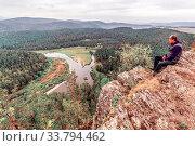 Купить «Mature man A tourist sits on a rock and looks afar to the Ural Mountains and the White River.», фото № 33794462, снято 7 сентября 2017 г. (c) Акиньшин Владимир / Фотобанк Лори