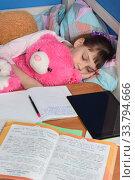 Купить «Girl fell asleep in a hug with a teddy bear doing lessons at home», фото № 33794666, снято 21 апреля 2020 г. (c) Иванов Алексей / Фотобанк Лори