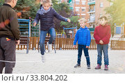 Купить «Children jump through an elastic rope in a children playground», фото № 33804202, снято 25 ноября 2018 г. (c) Яков Филимонов / Фотобанк Лори