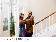 Caucasian couple having fun dancing and smiling in the hallway. Стоковое фото, агентство Wavebreak Media / Фотобанк Лори