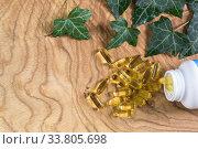 Прозрачные желатиновые овальные капсулы рыбьего жира рассыпались из флакона на деревянном фоне. Омега-3-незаменимые полиненасыщенные жирные кислоты. Место для текста. Стоковое фото, фотограф Наталья Гармашева / Фотобанк Лори