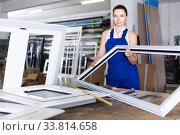 Купить «girl in workwear with window frame from pvc profile standing in workplace», фото № 33814658, снято 19 июля 2017 г. (c) Яков Филимонов / Фотобанк Лори