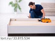 Купить «Young male contractor installing furniture at home», фото № 33815534, снято 11 ноября 2019 г. (c) Elnur / Фотобанк Лори