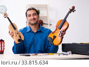 Купить «Young male repairman repairing violin», фото № 33815634, снято 25 октября 2019 г. (c) Elnur / Фотобанк Лори