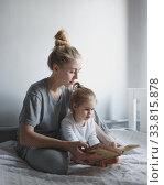 Купить «Мама и дочь читают книгу сидя к кровати», фото № 33815878, снято 10 февраля 2020 г. (c) Сергей Тиняков / Фотобанк Лори