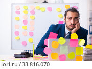 Купить «Young male employee in conflicting priorities concept», фото № 33816070, снято 4 октября 2019 г. (c) Elnur / Фотобанк Лори