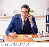 Купить «Young handsome employee planning his work activity», фото № 33817154, снято 1 августа 2018 г. (c) Elnur / Фотобанк Лори