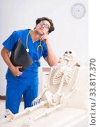 Купить «Funny doctor with skeleton in hospital», фото № 33817370, снято 11 июля 2018 г. (c) Elnur / Фотобанк Лори