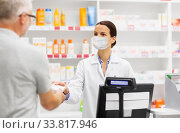 apothecary in mask and senior customer at pharmacy. Стоковое фото, фотограф Syda Productions / Фотобанк Лори
