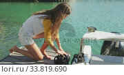 Купить «Side view of a teenage Caucasian girl untying a rope on the boat harbor side», видеоролик № 33819690, снято 4 февраля 2020 г. (c) Wavebreak Media / Фотобанк Лори