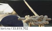 Купить «Close up detail of a knot in a rope securing a boat tied to a jetty», видеоролик № 33819702, снято 4 февраля 2020 г. (c) Wavebreak Media / Фотобанк Лори