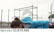 Купить «Sporty Caucasian woman exercising in an outdoor gym during daytime», видеоролик № 33819986, снято 8 августа 2019 г. (c) Wavebreak Media / Фотобанк Лори