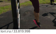 Купить «Sporty Caucasian woman exercising in an outdoor gym during daytime», видеоролик № 33819998, снято 8 августа 2019 г. (c) Wavebreak Media / Фотобанк Лори