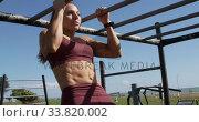 Купить «Sporty Caucasian woman exercising in an outdoor gym during daytime», видеоролик № 33820002, снято 8 августа 2019 г. (c) Wavebreak Media / Фотобанк Лори