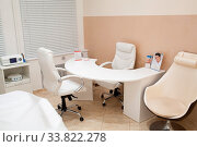Купить «Interior decor of the salon of a beautician and cosmetician with a modern curved desk, equipment and chairs in a neutral decor of white and beige», фото № 33822278, снято 28 мая 2020 г. (c) age Fotostock / Фотобанк Лори