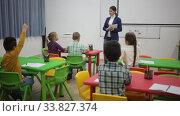 Купить «Group of cheerful studious pupils studying in elementary school, raising hands to answer female teacher», видеоролик № 33827374, снято 29 января 2020 г. (c) Яков Филимонов / Фотобанк Лори