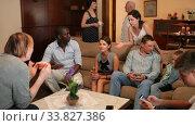 Three generations of happy multiethnic family lively talking together in cozy apartment. Стоковое видео, видеограф Яков Филимонов / Фотобанк Лори