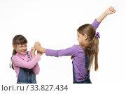 Одна девочка постарше лупит кулаками другую девочку. Стоковое фото, фотограф Иванов Алексей / Фотобанк Лори