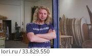 Купить «Caucasian male surfboard maker leaning on a door frame of the entrance with his arms crossed», видеоролик № 33829550, снято 6 марта 2020 г. (c) Wavebreak Media / Фотобанк Лори