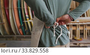 Купить «Caucasian male surfboard maker putting on a protective apron in his studio», видеоролик № 33829558, снято 6 марта 2020 г. (c) Wavebreak Media / Фотобанк Лори
