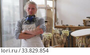Caucasian male surfboard maker wearing a face mask and standing in his studio with his arms crossed. Стоковое видео, агентство Wavebreak Media / Фотобанк Лори