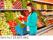Купить «Junge Frau als Kundin hält eine frische Paprika beim Gemüse kauf im Supermarkt», фото № 33831662, снято 5 июня 2020 г. (c) age Fotostock / Фотобанк Лори