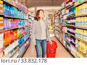 Купить «Lächelnde Frau mit Einkaufswagen beim Shopping im Discounter oder Supermarkt», фото № 33832178, снято 5 июня 2020 г. (c) age Fotostock / Фотобанк Лори