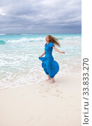 Купить «Slender young woman with long hair fluttering in the wind in a blue dress on the shore of a stormy sea on a sandy beach (Cuba, Varadero)», фото № 33833270, снято 2 июня 2020 г. (c) easy Fotostock / Фотобанк Лори