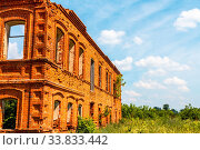 Купить «A big ruined ancient house of red brick against a blue sky with white clouds.», фото № 33833442, снято 26 мая 2020 г. (c) easy Fotostock / Фотобанк Лори