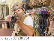 adult guy in military equipment with weapon in army shop. Стоковое фото, фотограф Яков Филимонов / Фотобанк Лори