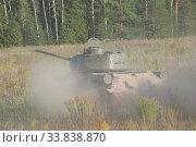 Купить «Советский средний танк времен Великой Отечественной войны Т-34-85 едет по полю в пыли, вид сзади», фото № 33838870, снято 25 августа 2018 г. (c) Малышев Андрей / Фотобанк Лори
