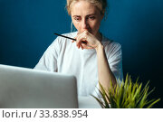 Купить «Сосредоточенная девушка смотрит в экран ноутбука», фото № 33838954, снято 23 мая 2020 г. (c) Сергей Тиняков / Фотобанк Лори