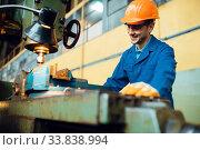 Turner in uniform and helmet works on lathe, plant. Стоковое фото, фотограф Tryapitsyn Sergiy / Фотобанк Лори