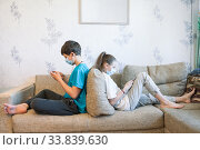 Pre-teen sister and brother gaming online with cellphones while sitting at home, children wearing safety masks, sitting back to back on sofa. Стоковое фото, фотограф Кекяляйнен Андрей / Фотобанк Лори