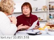 Купить «Frustrated senior lady with documents with female», фото № 33851518, снято 22 ноября 2017 г. (c) Яков Филимонов / Фотобанк Лори